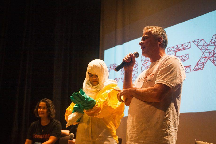 Junia Cajazeiro (esq) e Marcos Leitão (dir) fizeram uma dinâmica com uma voluntária da plateia (centro) e mostraram as dificuldades de trabalhar com o equipamento de proteção em surtos de doenças altamente contagiosas como o Ebola. (Foto: Lucca Mezzacappa)